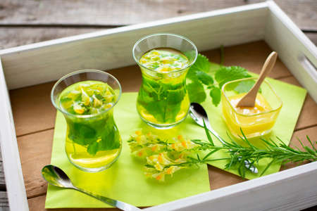 two freshly brewed teas of lemon balm and linseed in Turkish tea glasses on a tray Reklamní fotografie - 153453518