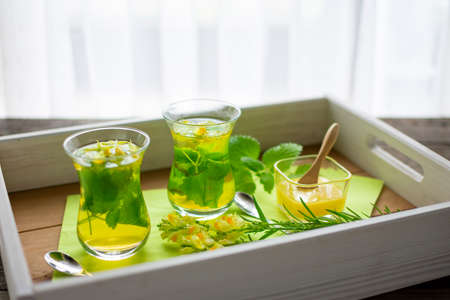 two freshly brewed teas of lemon balm and linseed in Turkish tea glasses on a tray Standard-Bild