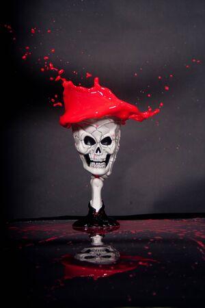 red liquid spilling over skeleton goblet photo