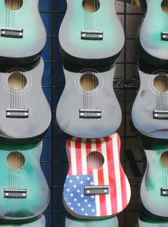 artisanry: An American painted guitar nestled in with plain guitars in store