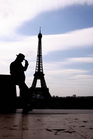 silhoetted man leaning against wall in front of the Eiffel Tower photo