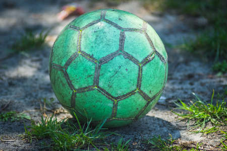 green soccer ball lies on the ground