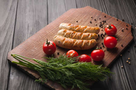 Grilled sausages grilled on a brown wooden board on a wooden background, six cherry tomatoes, greens, parsley dill, pepper, sauce.
