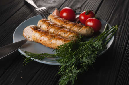 Three grilled sausages on a gray plate on a wooden black background lie also a cherry tomato, greens, garlic, knife, fork. View from above.