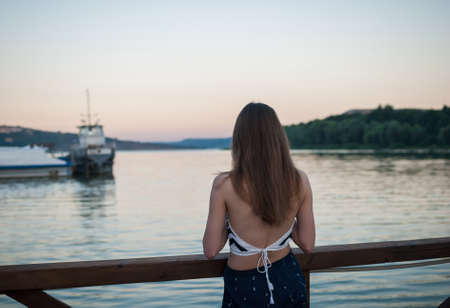 Girl is looking into the distance of the river against the background of the fjords at sunset, view from the back. Bakota, Ukraine