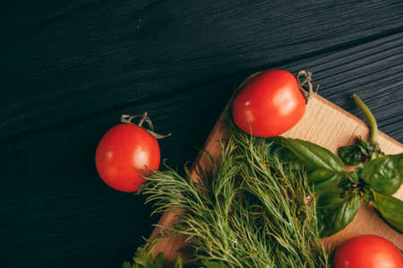 Tomatoes, parsley and dill on a wooden cutting board on a black wooden background.
