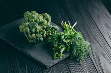 On a dark wooden table, fresh green broccoli, parsley, dill for your health. Flatlay. Recipe. Ingredients. Dietary food. Place under the text