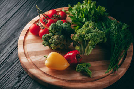 Fresh vegetables: cherry tomatoes, broccoli, pepper, dill, parsley on a round wooden board, on a dark wooden table. Recipe. Ingredients. Dietary food. Place under the text. View from above 스톡 콘텐츠