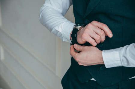 Hombre mirando reloj de lujo. El día de la boda del novio