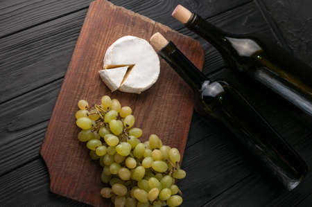 Bottles of wine on a black wooden background with grapes and cheese Camemberg