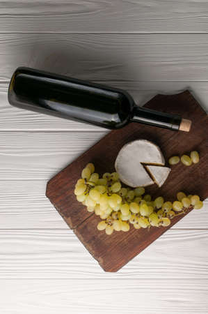 Bottles of wine on a white wooden background with grapes and Camembert cheese