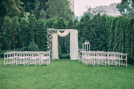 Beautiful wedding set up. Area of the wedding ceremony. Round arch, white chairs decorated with flowers, greenery. Cute, trendy rustic decor. Part of the festive decor, floral arrangement. Imagens