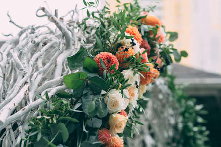Square wedding ceremony. The round arch is decorated with flowers, greenery. Cute, trendy wedding decor. Part of the festive decor, flower arrangement.