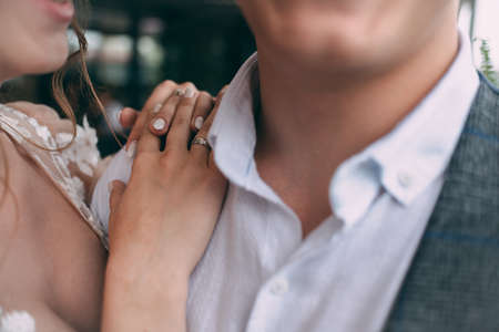 Sensual portrait of a young couple. Wedding photo outdoors, the bride holds her hand on the grooms shoulder, close-up. Concept Focus on the hand of the bride with a wedding ring.