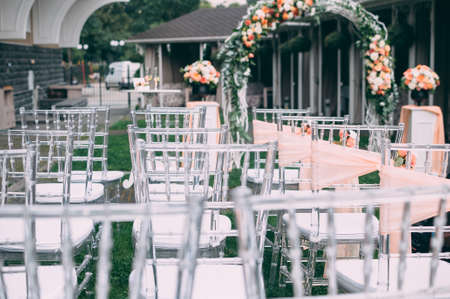Square wedding ceremony. Transparent chairs are decorated with flowers, greenery. Cute, trendy svdebany decor. Part of the festive decor, flower arrangement