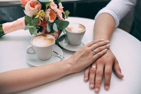 The bride and groom hold hands, holding expensive wedding rings with white gold, on the background of a wedding bouquet and two cups of coffee on a white table.
