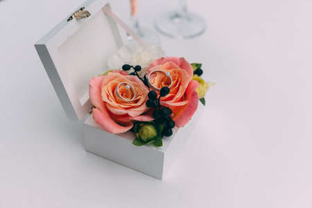 Two wedding glasses and bridal bouquet on stone in summer garden