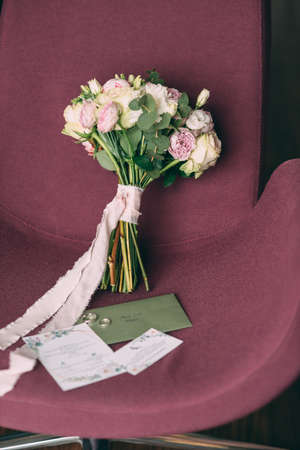 The bride's wedding bouquet in pink style, the bouquet is tied with a pink ribbon, next to it are invitations and wedding rings. Stok Fotoğraf - 143995799