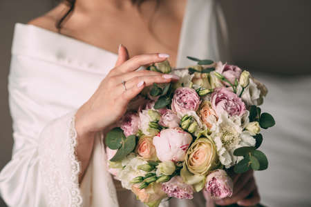 The bride holds in her hands a bridal bouquet of the bride in pink style, the bouquet is tied with a pink ribbon. The bride wears a beautiful white bathrobe. Stok Fotoğraf - 143997018