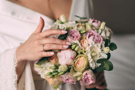 The bride holds in her hands a bridal bouquet of the bride in pink style, the bouquet is tied with a pink ribbon. The bride wears a beautiful white bathrobe.