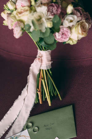 The bride's wedding bouquet in pink style, the bouquet is tied with a pink ribbon, next to it are invitations and wedding rings. Stok Fotoğraf - 143998823