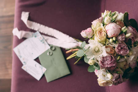 The bride's wedding bouquet in pink style, the bouquet is tied with a pink ribbon, next to it are invitations and wedding rings. View from above. Stok Fotoğraf - 143998835