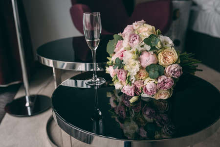 The bride s wedding bouquet in pink style, the bouquet is tied with a pink ribbon, lies on a black mirror table in the room.