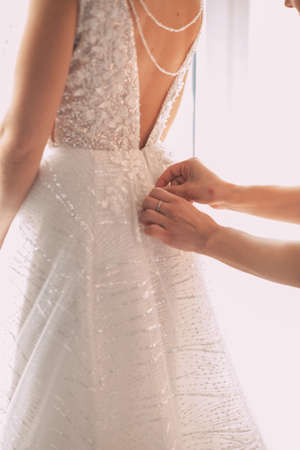 Bridesmaid makes bow-knot on the back of brides wedding dress Stok Fotoğraf - 144407266