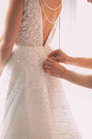 Bridesmaid makes bow-knot on the back of brides wedding dress Stok Fotoğraf