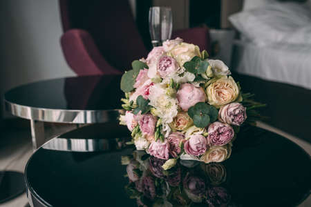 The bride s wedding bouquet in pink style, the bouquet is tied with a pink ribbon, lies on a black mirror table in the room. Stok Fotoğraf - 144408277