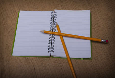 open  notebook on a wooden desk with pencil photo