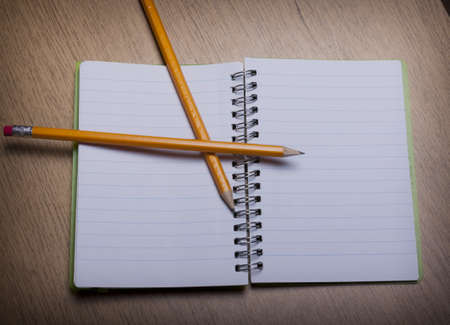 open  notebook on a wooden desk with pencil Stock Photo - 15312267