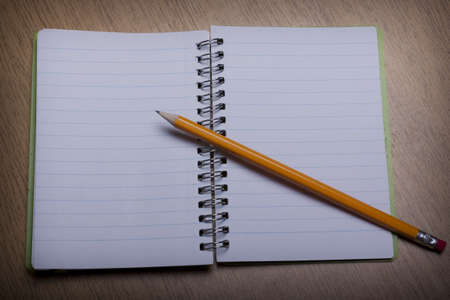 diagonal diary education: open  notebook on a wooden desk with pencil