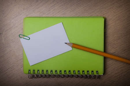 green notebook on a wooden desk Stock Photo - 15312271