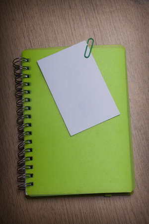 green notebook on a wooden desk Stock Photo - 15312272