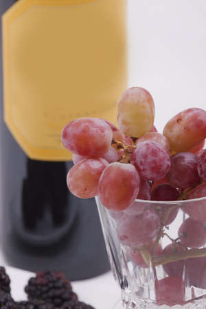 Bottle of red wine, and glass filled with grapes photo