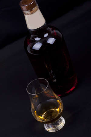 glass and bottel of whisky on a black background photo