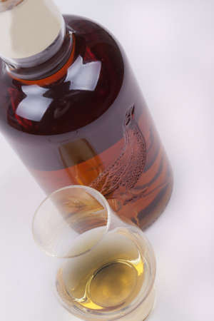 glass and bottle of scotish whisky on a white background photo