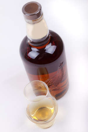 glass and bottle of whisky on a white background Stock Photo