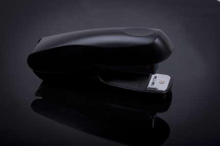 a stapler on a black shiny background