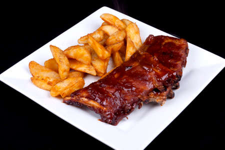 BBQ ribs with potato wedges on a white plate.