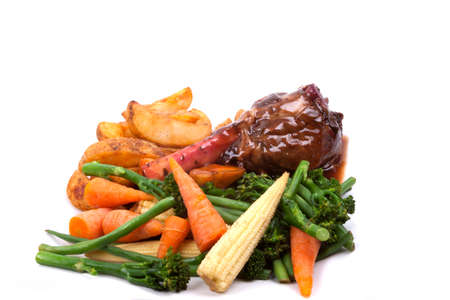jus: Lamb Shank in a Rosemary and Red Wine Jus with vegetable on a white plate