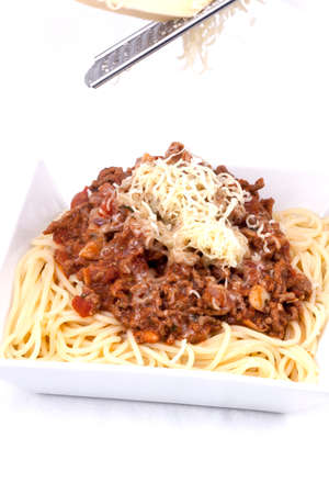 Spaghetti bolognese, topped with basil and shaved parmesan cheese