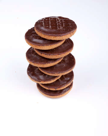 Pile of chocolate coated jaffa cakes with a segment of orange on a white background.