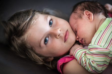 Portrait of a cute little girl hugging to her chest newborn sleeping sister