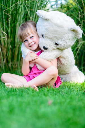 Little cute girl sittinging in the grass with large teddy bear on her back photo