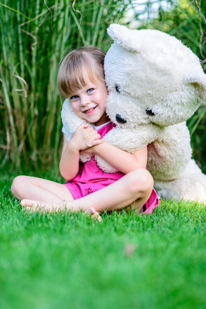 Little elfin girl sitting in the grass with large teddy bear photo