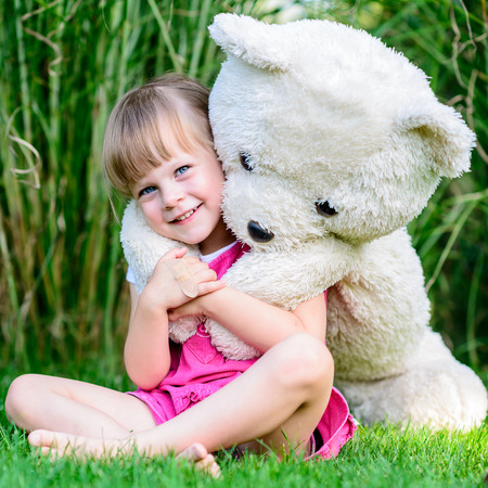 Little cute girl sitting in the grass with large teddy bear on her back photo