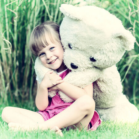 Little cute girl sitting in the grass with large teddy bear on her back - Vintage version photo