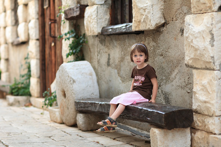 suprise: Suprised Little girl sitting on an old wooden bench